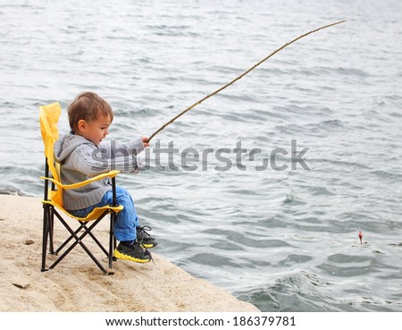 Little boy catching a fish. Happy holidays concept. - stock photo