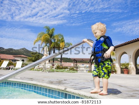 Little Boy Cautiously Stepping into Outdoor Pool in San Diego, California - stock photo