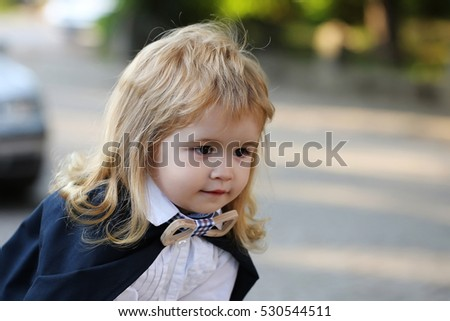 Little boy child in black academic gown and school bow tie with long blonde hair on emotional face outdoor