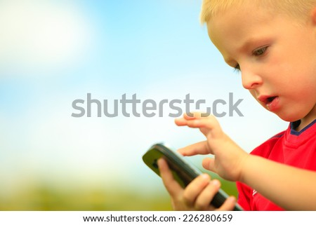 Little boy child kid  playing games on smartphone mobile phone outdoor. Technology generation. - stock photo