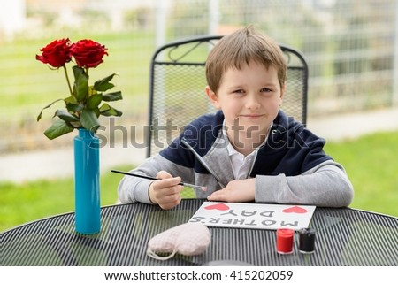 Little boy child painting greeting card for his mother on Mother's Day. - stock photo