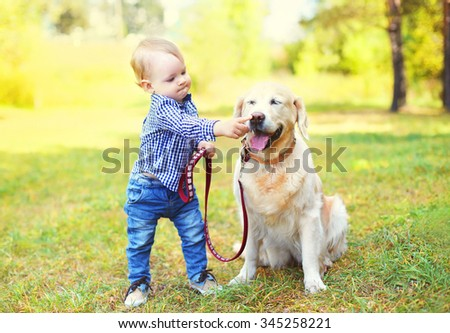 Little boy child playing with Golden Retriever dog on grass in park
