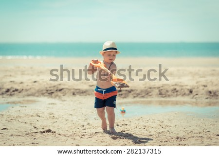 little boy child walking at the camera with a shovel in his hands on the beach - stock photo