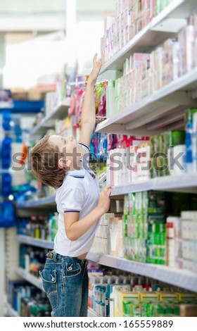 Little boy chooses cosmetics on the shelves of the market - stock photo