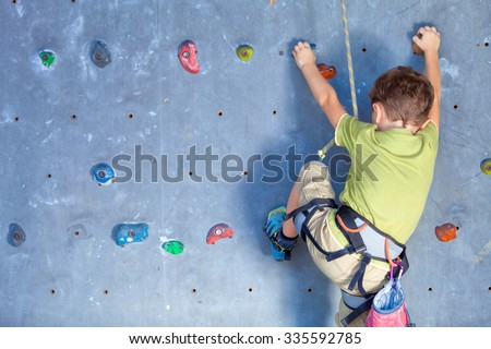 little boy climbing a rock wall indoor - stock photo