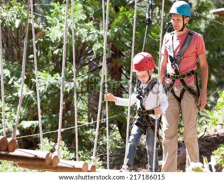 little boy climbing at adventure park with his father - stock photo