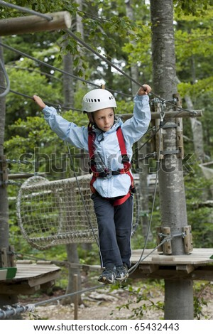Little boy climbing in adventure park - stock photo