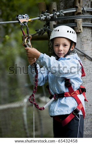 Little boy climbing in adventure park - stock photo