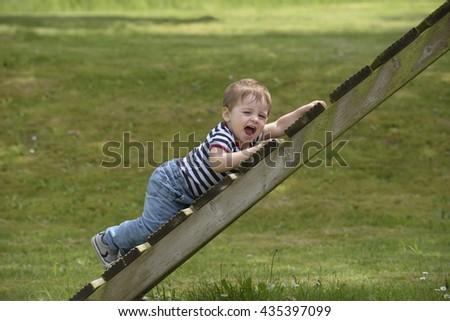 Little boy climbing on garden toys - stock photo