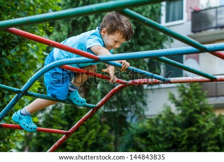 Little boy climbing on jungle gym without rope and helmet on playground, dangerous - stock photo