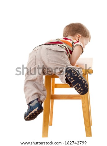 Little boy climbing on stool, isolated on white - stock photo
