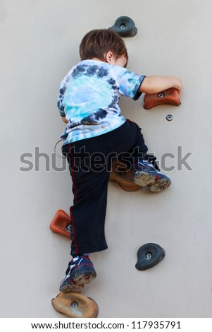 Little boy climbing on wall without rope and helmet dangerous - stock photo