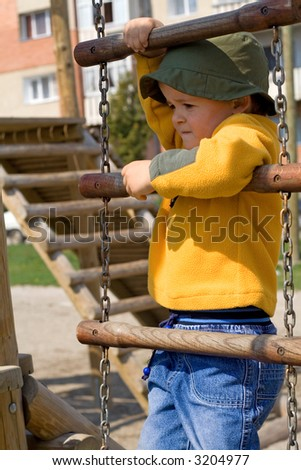 Little boy climbing up a chain ladder on the playground - stock photo
