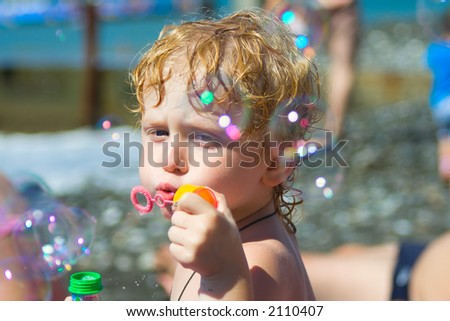 little boy concentrated on blowing soap bubbles, focused on face, bubbles unfocused - stock photo
