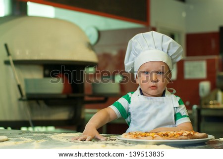 Little boy cooking pizza - stock photo