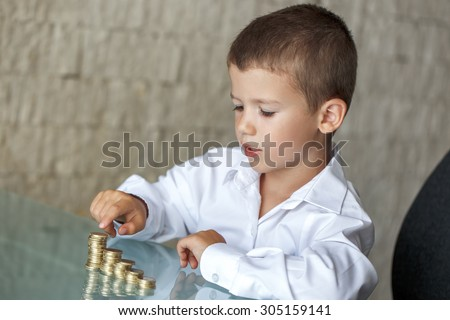 Little boy counting coins on glass desk in office - stock photo