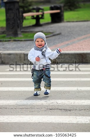 Little boy crossing a street - stock photo