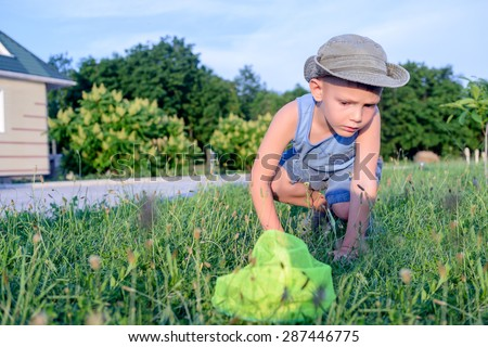 Little boy crouching down searching in the grass for insects to catch with his yellow net in evening light - stock photo
