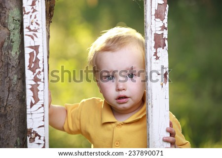 Little boy crying  in garden. - stock photo