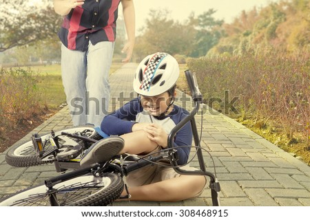 Little boy crying on the road while holding his knee after falling from the bicycle with dad on the back - stock photo