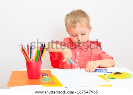 little boy cutting from paper, early learning and daycare concept - stock photo