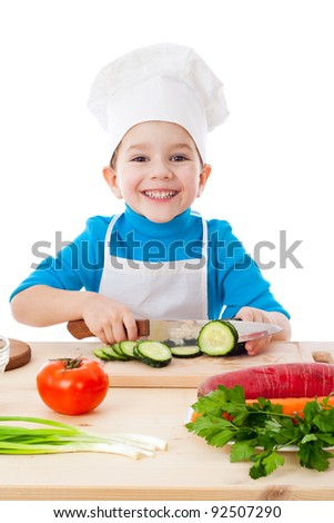 Little boy cutting the cucumber, isolated on white