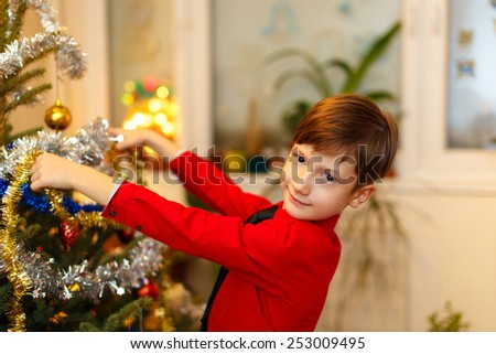 Little boy decorating christmas tree at home - stock photo