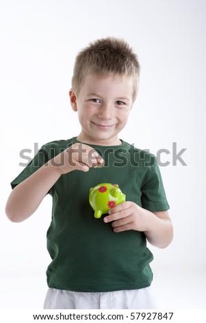 Little boy depositing money in his piggy bank. Concept: my future - stock photo