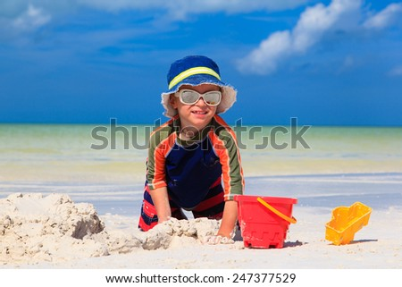 little boy digging sand on tropical sand beach