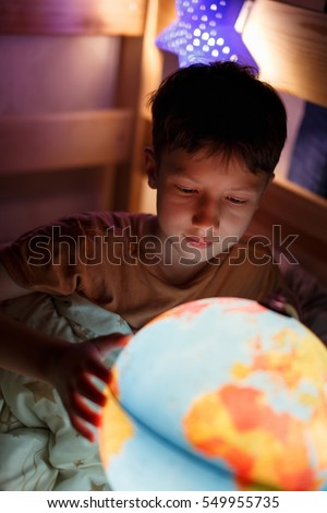 Little boy discovering countries on globe at night, studying in bed
