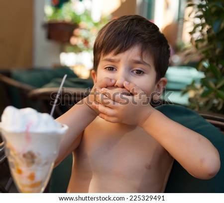 Little boy does not want to eat ice cream dessert - stock photo