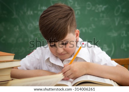 Little boy doing homework or writing during class - stock photo