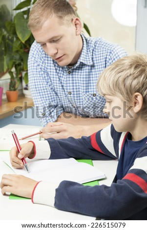 Little boy doing homework with father, vertical