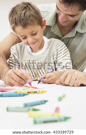 little boy doing paint homework with his father at home