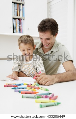 little boy doing paint homework with his father at home - stock photo
