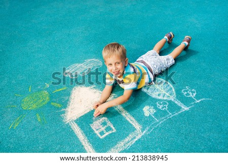 Little boy drawing chalk image on the ground - stock photo
