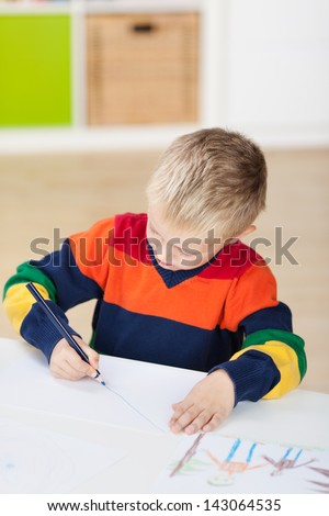 Little boy drawing on paper at table in house