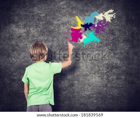 Little boy drawing on the wall. - stock photo