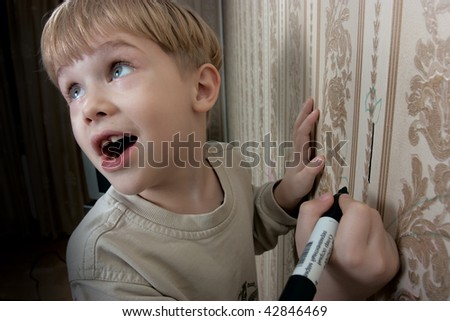 little boy drawing on the wall - stock photo