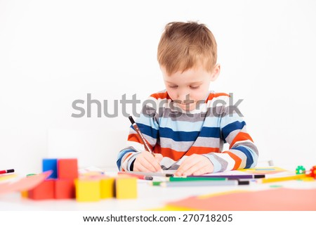 Little boy drawing picture while sitting at his desk