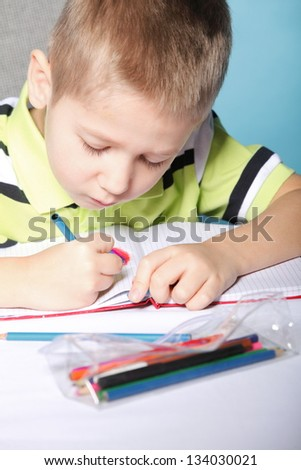 little boy drawing with color pencils on blue background