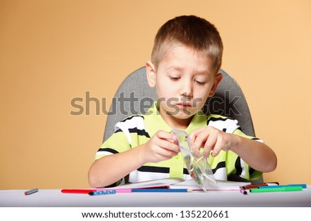 little boy drawing with color pencils on orange background