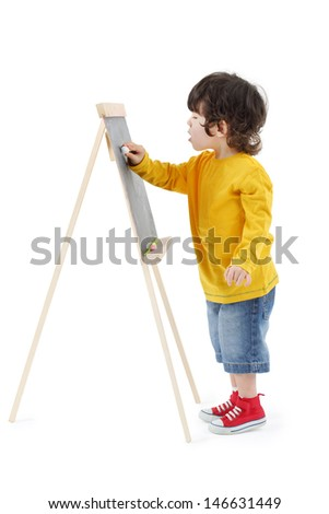 Little boy draws with chalk on chalkboard isolated on white background. - stock photo