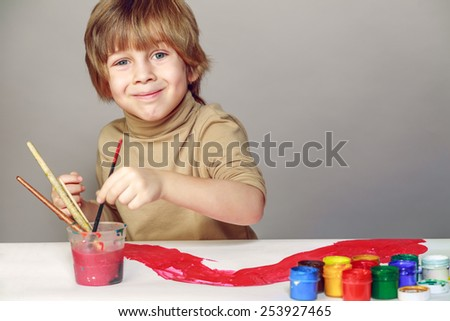 little boy draws with colored inks on paper paints - stock photo