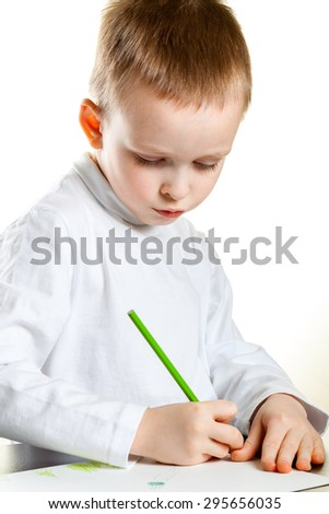 little boy draws with colored pencils drawing - stock photo