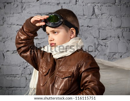Little boy dreaming of becoming a pilot in retro style uniform