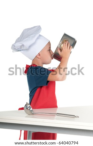 Little boy dressed as a chef tasting the food he made from the pan - stock photo