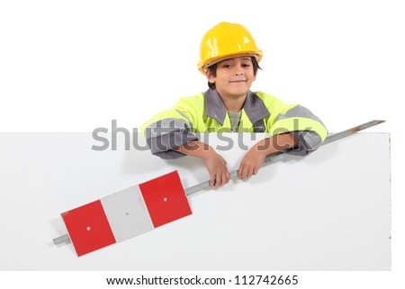 little boy dressed as a road worker holding a traffic sign - stock photo