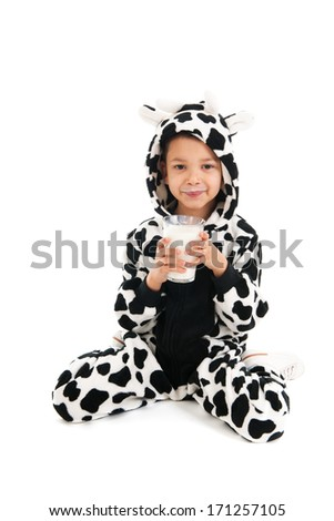 Little boy dressed as cow drinking healthy glass of milk - stock photo