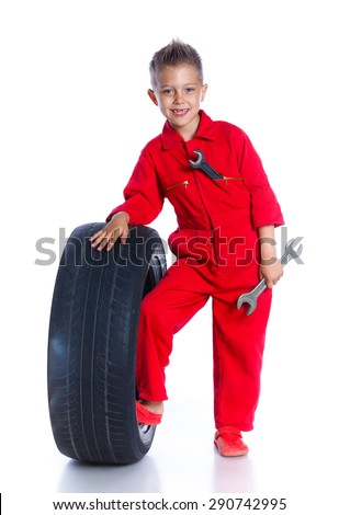 Little boy dressed as mechanic with tire and adjustable wrench. Isolated on white background - stock photo